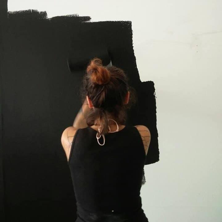 Die Autorin streicht ihre Wand schwarz