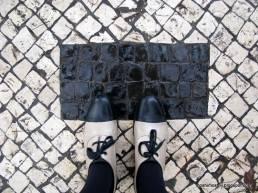 weiße Schuhe mit schwarzer Spitze auf weißem Pflaster mit schwarzen Rechteck